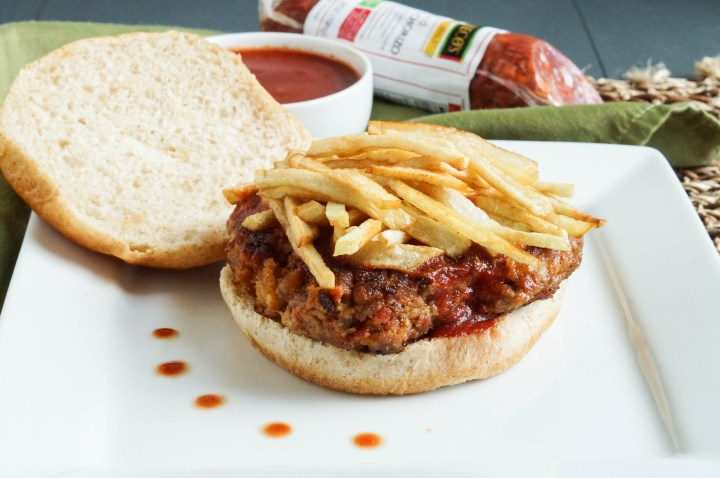 Frita Cubana (Cuban Hamburger) on a square white plate with fries on top.