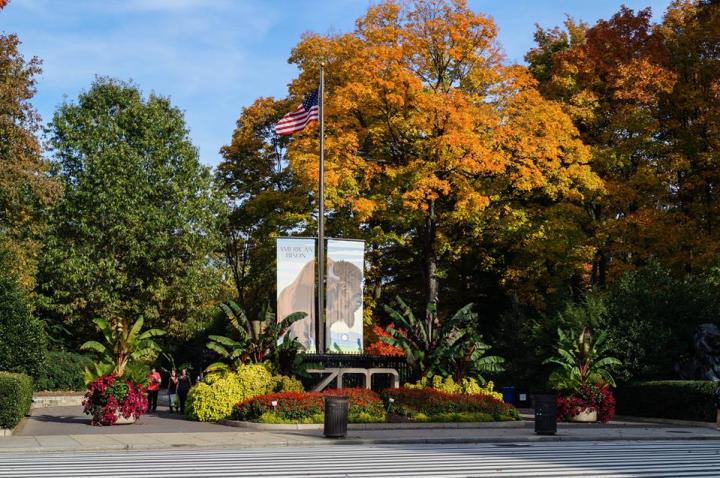 Smithsonian National Zoological Park entrance with fall trees and a banner with a bison.