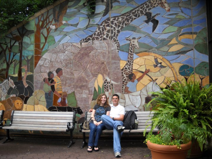 Sitting on a bench in front of a mosaic mural with people, elephants, birds, and giraffes.
