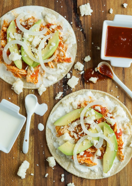 Aerial view of Chicken Tinga on two tortillas with scatter crumbled cheese, crema, chipotle sauce, avocado, and onion.