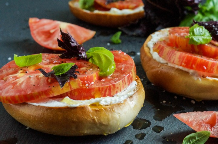 Two Crisp Toasted Bagels with Fromage Blanc, Tomato, Sea Salt, and Basil.