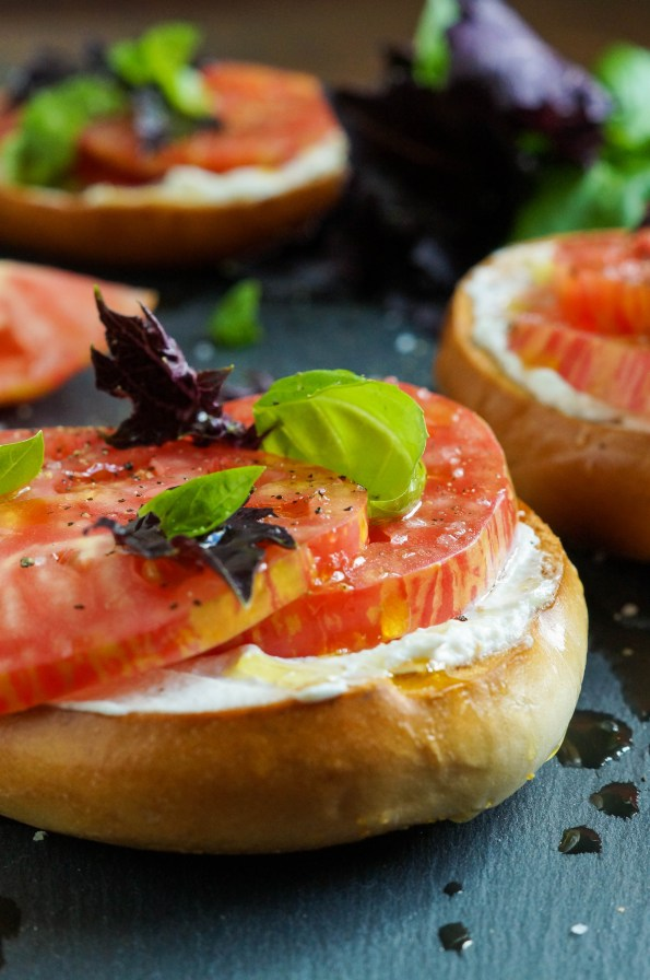 Close up of Crisp Toasted Bagels with Fromage Blanc, Tomato, Sea Salt, and Basil topped with green and purple basil leaves.