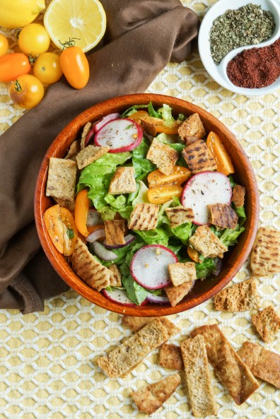 Aerial view of Fattoush in a wooden bowl with pita and cherry tomatoes