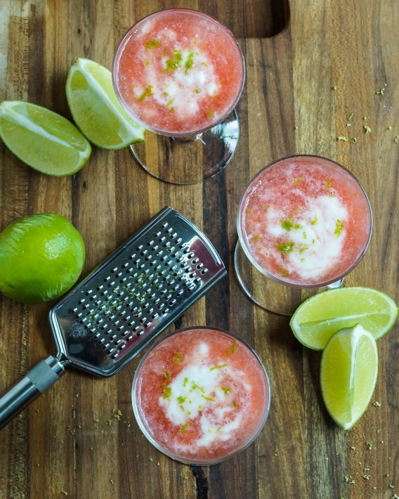 Aerial view of Watermelon Yogurt Cooler in three glasses next to lime wedges and a zester.