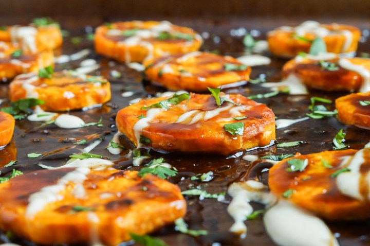 Close up of Sweet Potatoes with Tamarind and Tahini on a baking sheet, drizzled with sauce, and topped with fresh cilantro.