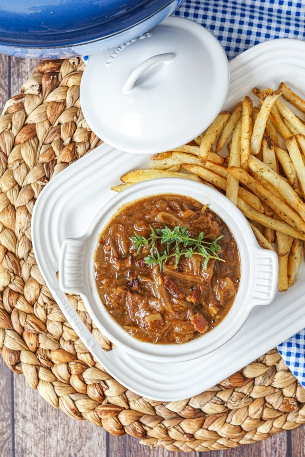 Aerial view of Carbonnade Flamande (Flemish Beef and Beer Stew) in a white bowl on a white platter next to fries.