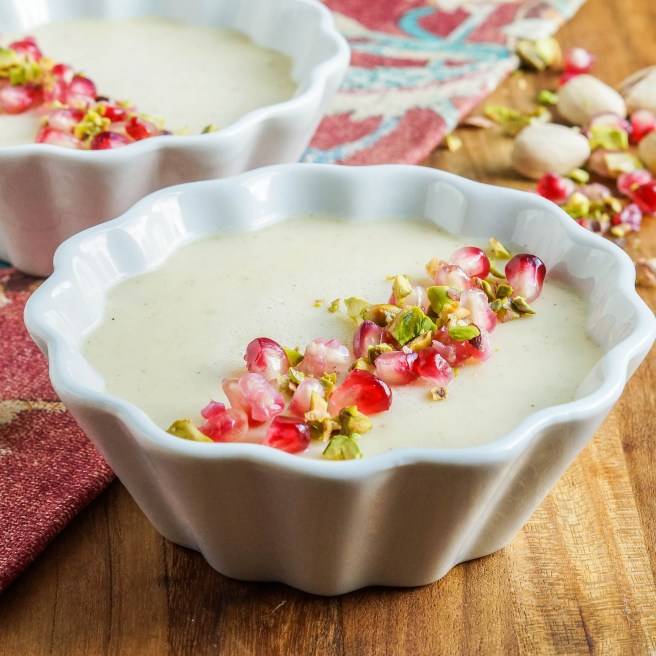 Mishti Dohi (Indian Baked Sweet Yogurt Cream) in two white ramekins and topped with pistachios and pomegranates.