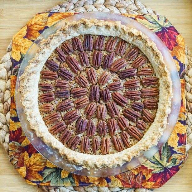 Aerial view of Pecan Pie in a clear pie dish over a fall leaf towel.