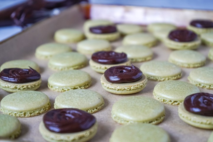 Piped ganache over Matcha Macarons on a baking sheet.