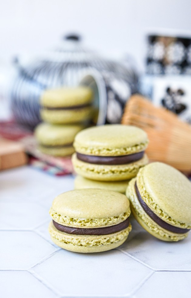 Side view of a stack of Matcha Macarons with Chocolate Ganache in front of a black and white tea set.