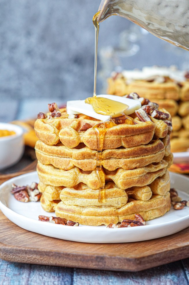 Pouring maple syrup over a stack of five Sweet Potato Waffles.