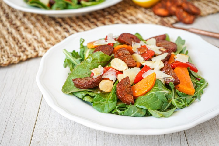 Side view of chorizo and Sweet Potato Salad on a white plate.