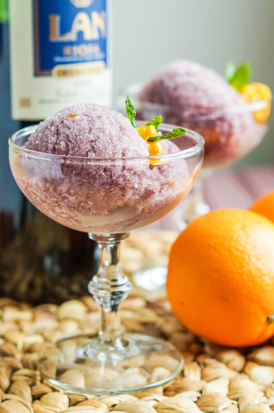 Side view of Sorbete de la Rioja (Rioja Wine Sorbet) in two clear glasses next to an orange and red wine bottle.