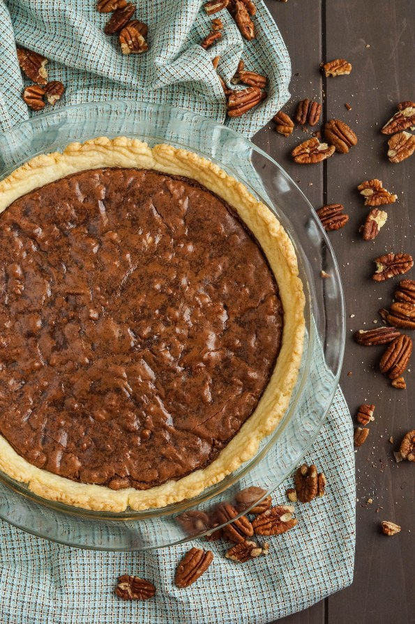 Aerial view of Brownie Pecan Pie in a clear pie dish next to scattered pecans.