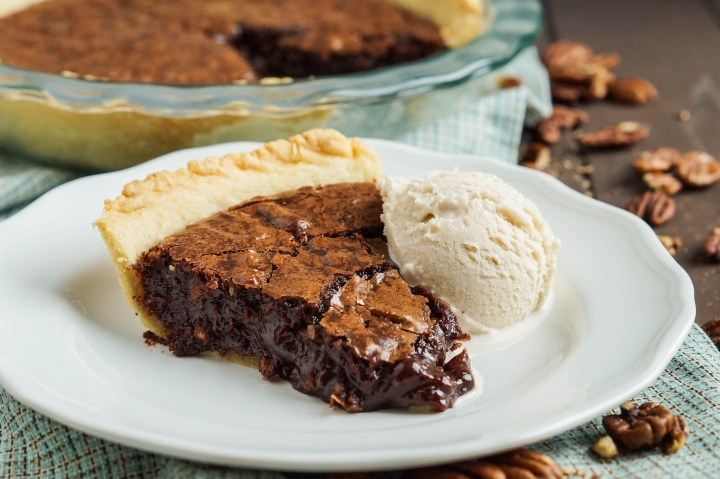 A slice of Brownie Pecan Pie on a white plate with a scoop of vanilla ice cream.