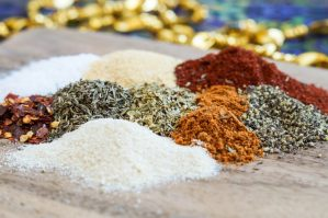 Piles of spices on a wooden board for Cajun Spice Mix.