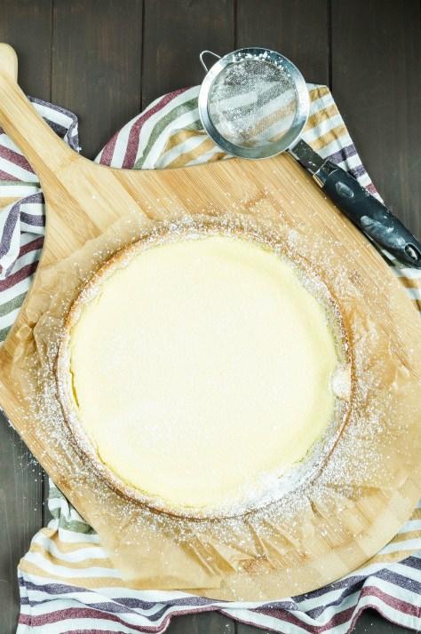 Badischer Rahmkuchen (Baden-Style Cheesecake) on a wooden board topped with powdered sugar