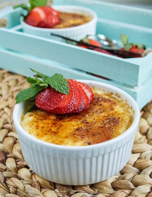 Close up of Strawberry Vanilla Yogurt Brûlée in a white ramekin with another in the background in a blue wooden tray.