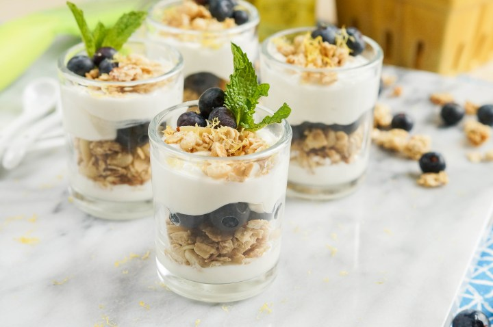 Lemon Blueberry Parfait in four glasses on a marble board.