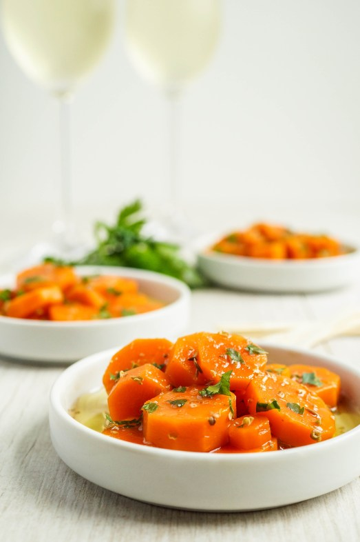 Side view of Zanahorias Aliñadas (Spanish Marinated Carrots) on three small white plates with parsley and two wine glasses in the background.