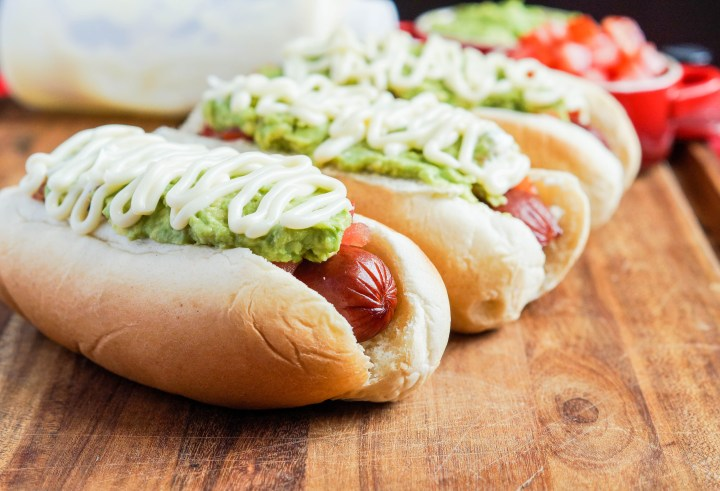 Three Completo Italiano (Chilean Italian-Style Hot Dogs) on a wooden board with tomatoes, avocado, and drizzled mayonnaise.