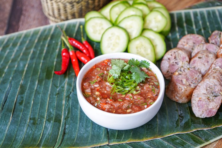 Jeow Mak Len (Lao Tomato Dipping Sauce) in a white bowl on a banana leaf.