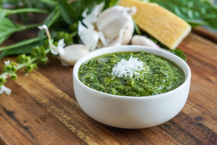 Pistou (Provençal Basil Paste) in a small white bowl with garlic and basil in the background.