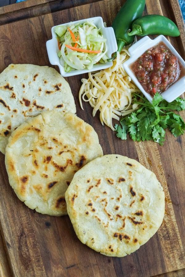 Aerial view of three Pupusas de Queso (Salvadoran Cheese-Stuffed Tortillas) on a wooden board.