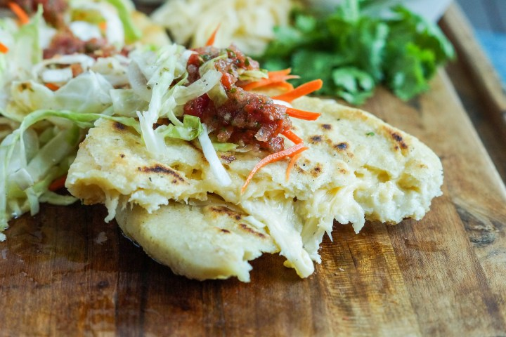 Close up of torn Pupusas de Queso (Salvadoran Cheese-Stuffed Tortillas) on a wooden board with cheese showing.