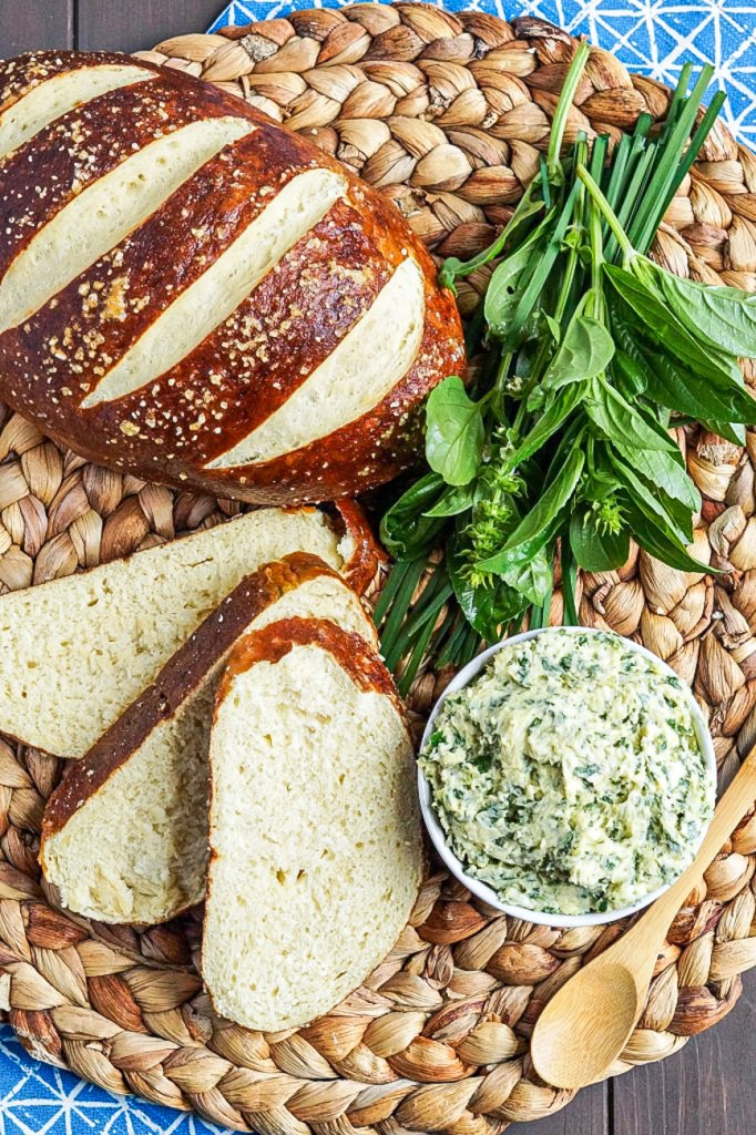 Aerial view of Kräuterbutter (German Herb Butter) next to pretzel bread, a bunch of basil, and a wooden spoon.