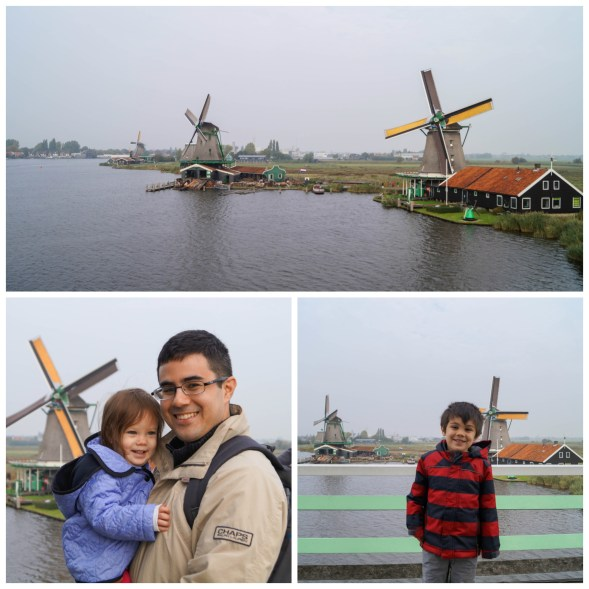 Windmills along the water at Zaanse Schans, standing in front of the windmills.