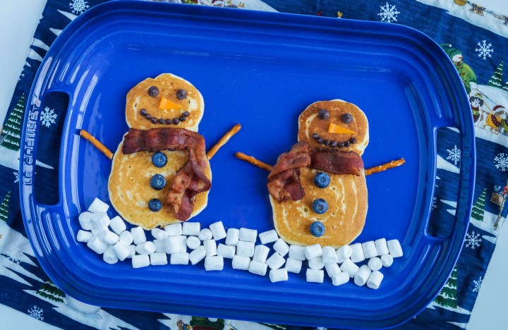 Aerial view of two Snowman Pancakes on a blue platter with a layer of mini marshmallows for snow.