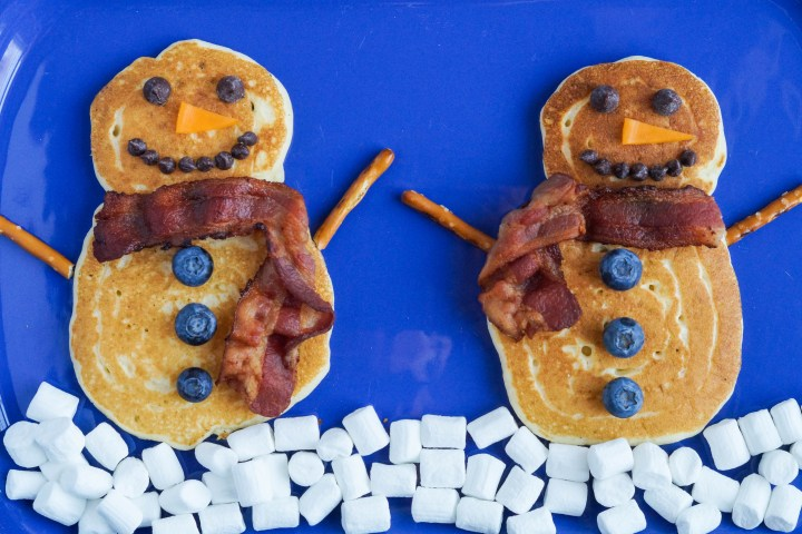 Snowman Pancakes on a blue platter with a layer of mini marshmallows for snow.