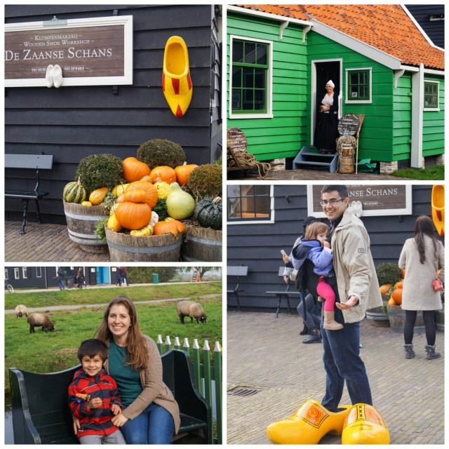 Black and green buildings at Zaanse Schans with a sign stating- De Zaanse Schans, pumpkins in the front and large clogs on display.