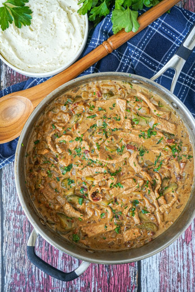 Aerial view of Kurzemes Strogonovs (Latvian Pork Stroganoff) in a pan next to a bowl of mashed potatoes.