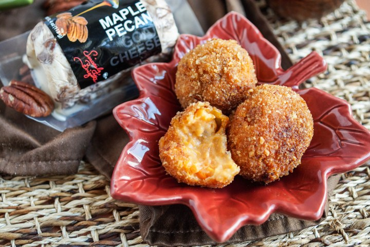 Three Sweet Potato Maple Pecan Goat Cheese Croquettes on a red leaf plate next to a container of maple pecan goat cheese.