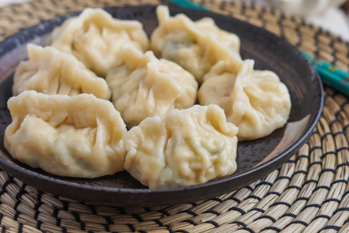 Seven Spinach and Egg Dumplings on a dark brown plate.