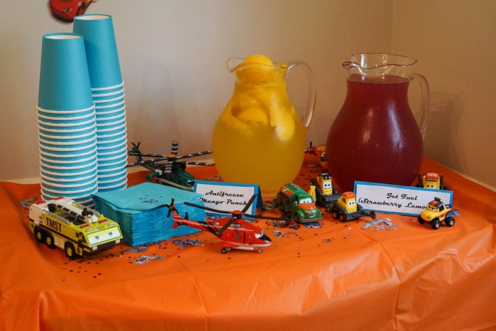 Cars and Planes drink table with two glass pitchers, paper cups, and cars/planes toys.