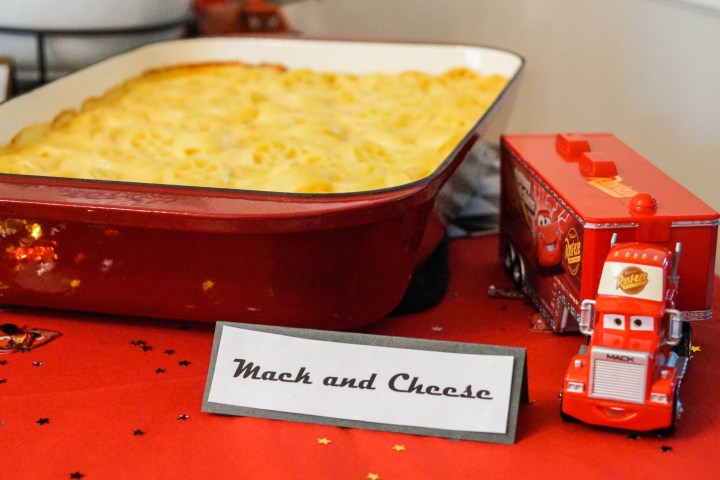 Macaroni and Cheese in red pan with sign- Mack and Cheese.