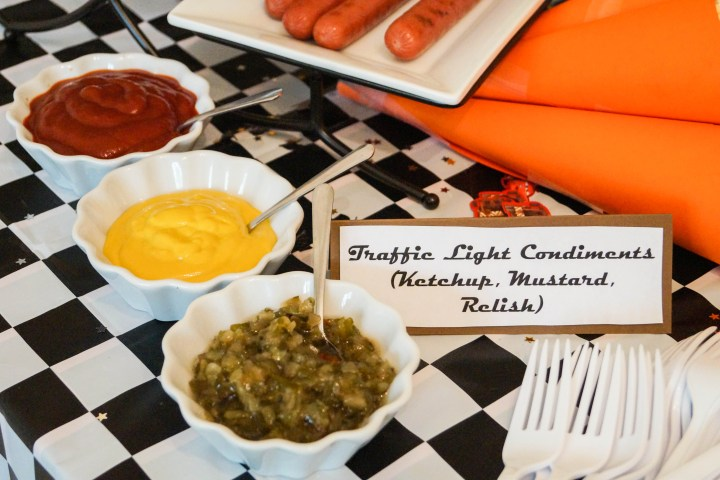 Relish, mustard, and ketchup in three white bowls with sign- Traffic Light Condiments.