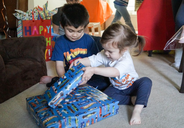 Brother and sister sitting together with two presents.