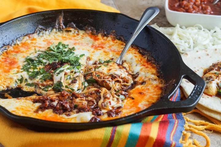 Queso Fundido (Melted Cheese with Chorizo) in a cast iron skillet with a metal spoon.