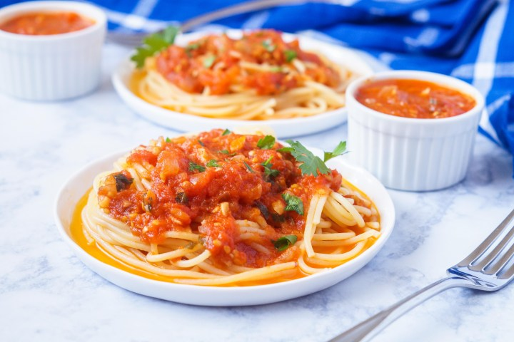 Šalša (Croatian Tomato Sauce) over spaghetti on two white plates.