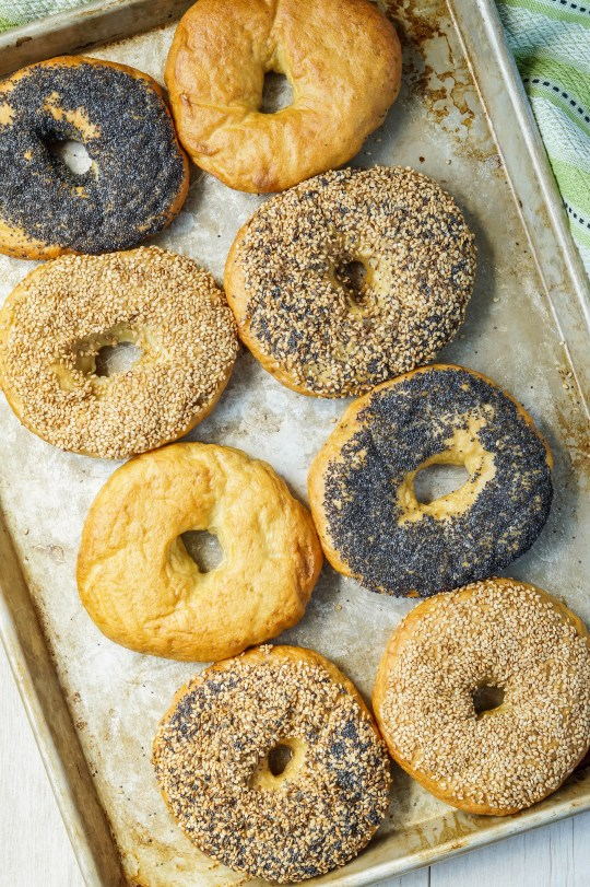 Aerial view of 8 Bagels on a silver baking sheet with a variety of toppings.