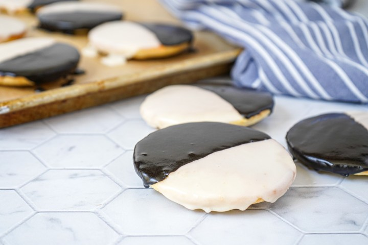 Three Black and White Cookies with more in the background on a baking sheet.