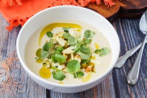 Moorish Chilled Almond and Orange Blossom Soup with Apple and Watercress Dressing in a white bowl.