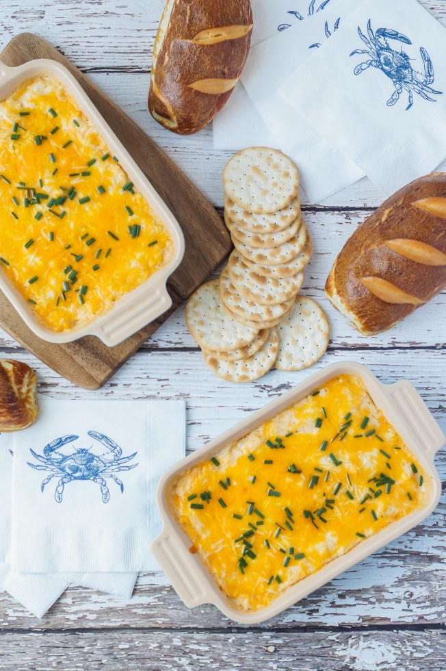 Aerial view of Maryland Crab Dip in two rectangular dishes alongside crackers and pretzel bread.