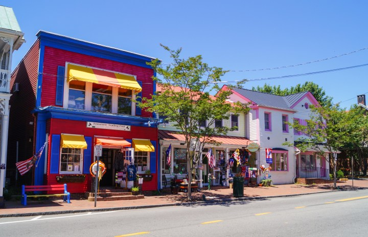 Street in St. Michaels lined with colorful buildings- one red and blue and another white with pink trim.