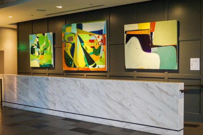 Bright abstract paintings lining the hallway wall at The Logan Hotel.