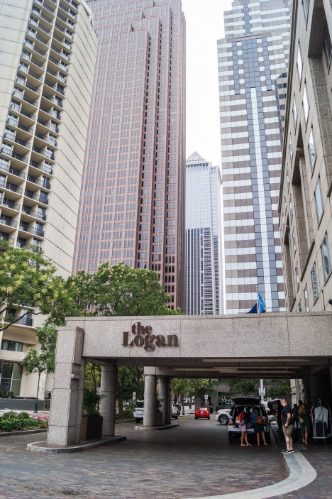 Outdoor entrance to The Logan Hotel with tall buildings in the background.